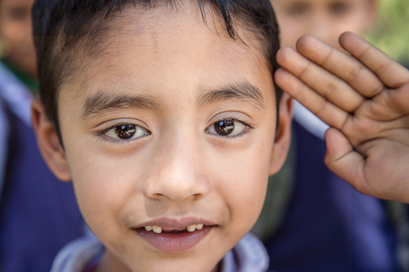 Portrait of adorable young Indian poor kid attending morning assembly in rural elementary school.