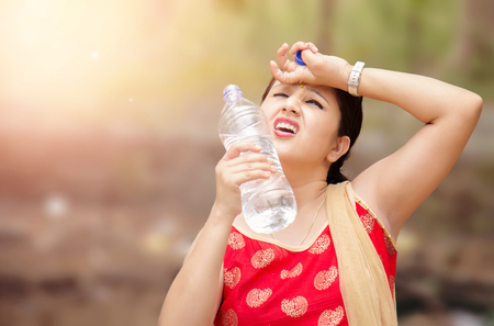 Young Indian woman holding water bottle during warm sunny day.