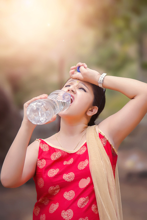 Young Indian woman holding water bottle during warm sunny day. Фото со стока