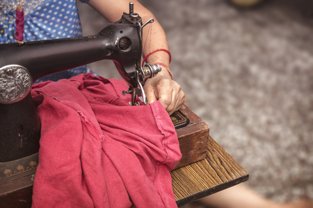 Indian Senior  women sitting cross-legged making clothes with old sewing machine