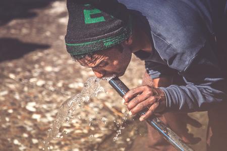 Man drinking water from broken water pipe