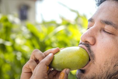 Indian man eating mango.