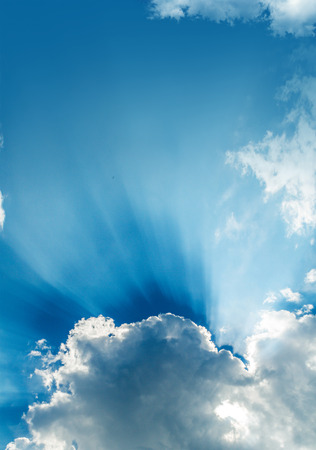 Sun rays bursting through clouds in a blue sky.