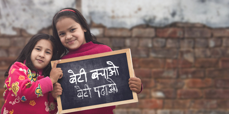 Adorable little 6-8 years old and 8-10 years old Asian girls smiling, holding beti bachao beti padhao chalkboard. Save and educate Daughter concept