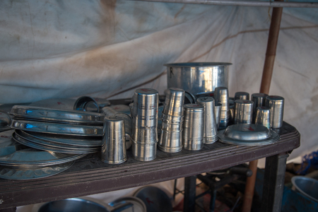 Close up of steel utensils bowls, pots and trays used by an old open kitchen restaurant in India