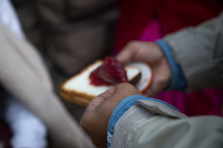 A hand putting jam on a piece of bread with spoons
