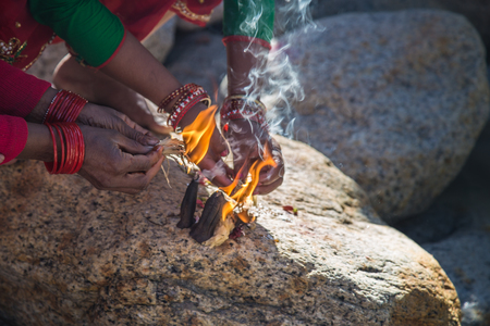 Womans hand put the incense stick near ganga ghat in India. It is a religious ritual. 版權商用圖片