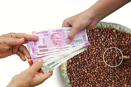 Hand Giving Indian 500 and 2000 Rupee Bank Notes over bag,burlap full of Coffee beans, concept for earnings or spend in Agriculture. Stockfoto