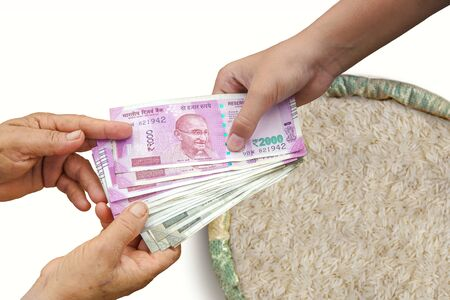 Hand Giving Indian 500 and 2000 Rupee Bank Notes over bag,Burlap full of Rice In Burlap Sack.