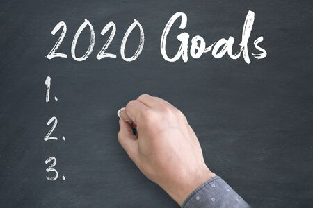 Thinking Position of A Young Asian Man while standing directly below blackboard with chalk drawing of new year 2020 Goals