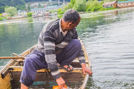 An old man removing water which has entered the broken boat.
