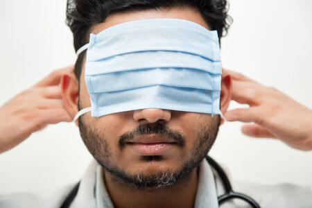 Doctor covering his eye with mask. concept of cold and flu, fever and coronavirus symptoms