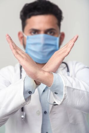 Portrait of Asian medical male Doctor wear a mask to prevent germs and standing and raising hand to show the symbol of wrong in white background. epidemic corona virus outbreak concept