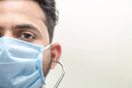 Close up portrait of adult female surgeon doctor wearing protective mask Half face closeup. Healthcare, medical education, emergency medical service and surgery concept