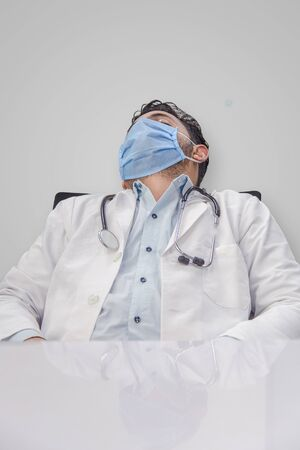 Coronavirus COVID-19 pandemic. Tired, exhausted doctor in uniform is sleeping in hospital desk or clinic after hard duty. male with mask and stethoscope around neck and closed eyes