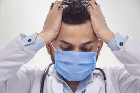 Desperate doctor holds his head up with hand. Concept of stress and failure at work. isolated on white.