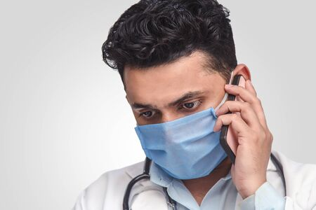 Portrait of Asian doctor on white background, talking on phone. Looking sad