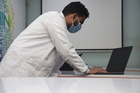 Asian doctor in white coat wearing mask and stethoscope working on laptop at clinic. Health care, therapy and counseling, medicine concept
