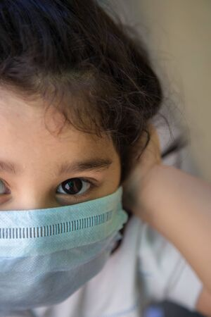 Close up of Indian baby girl wearing the mask for protect them self from virus and air pollution. Prevention by mask to reduce spread of the coronavirus covid-19 outbreak from human to human transmission.