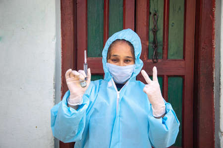 Young woman doctor in PPE protective mask and gloves holding a syringe and  vaccine, standing in front of village door showing victory sign. The concept of a new vaccine against the disease, flu vaccine vaccination