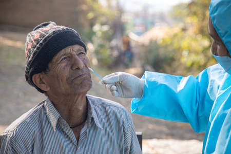test in India, Medic wear PPE suits collects swab sample from the nose of a woman for  test via Rapid Antigen, to curb the spread of coroavirus.