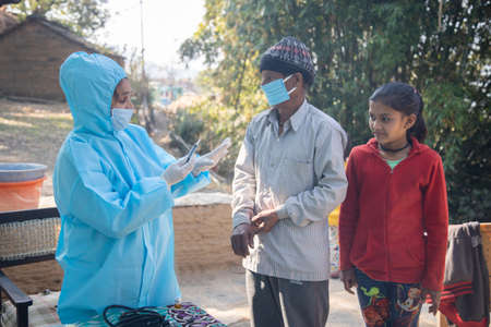 Young woman doctor in PPE protective mask and gloves holding a syringe and vaccine, standing with village people explaining importance of virus vaccine. The concept of a new vaccine against the disease, flu vaccine vaccination