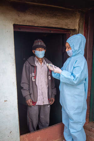 Young woman doctor in PPE protective mask and gloves holding a syringe and  vaccine, standing with village men explaining importance of  virus vaccine. The concept of a new vaccine against the disease, flu vaccine vaccination