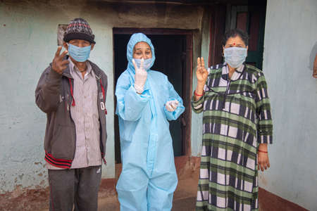 Young woman doctor in medical uniform holding a syringe and   vaccine, standing with village man and women explaining importance of  virus vaccine. The concept of a new vaccine against the disease, flu vaccine vaccination 免版税图像