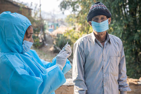 doctor in gloves holding syringe and making injection to patient.   vaccine. Vaccination in Indian village