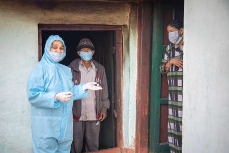 Young woman doctor in PPE protective mask and gloves holding a syringe and  vaccine, standing with village man and women explaining importance of  virus vaccine. The concept of a new vaccine against the disease, flu vaccine vaccination 免版税图像