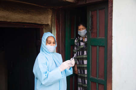 Young woman doctor in PPE protective mask and gloves holding a syringe and  vaccine, standing with village women explaining importance of  virus vaccine. The concept of a new vaccine against the disease, flu vaccine vaccination
