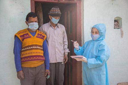 Women nurse workers in ppe kit doing door to door surveys in Indian village regarding