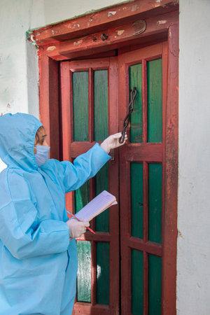 Women nurse workers in ppe kit doing door to door surveys in Indian village regarding  .The concept of a new vaccine against the disease, flu vaccine vaccination 免版税图像