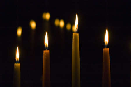 Four candles on black photo