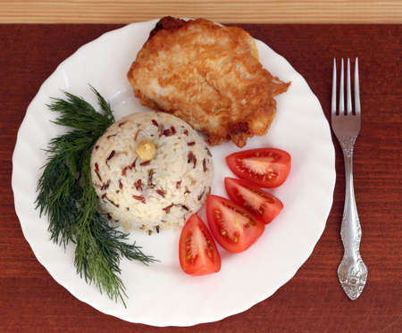 fried chicken fillet with wild and brown rice and tomatoes photo