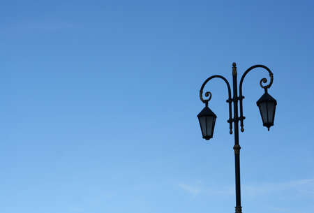 doubled: Old doubled street lamppost  against the blue sky Stock Photo