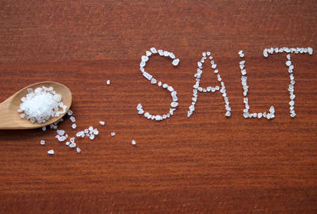 Sea salt in wooden spoon and letters from salt crystals photo