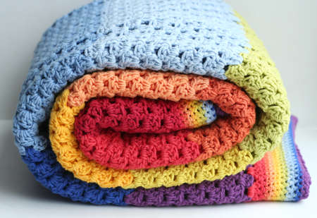 coziness: rainbow crocheted blanket, handmade Stock Photo