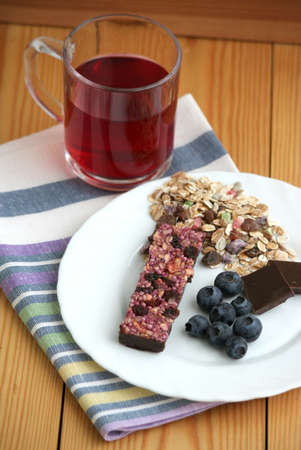 muesli snack bar, chocolate, blueberries and berry tea photo