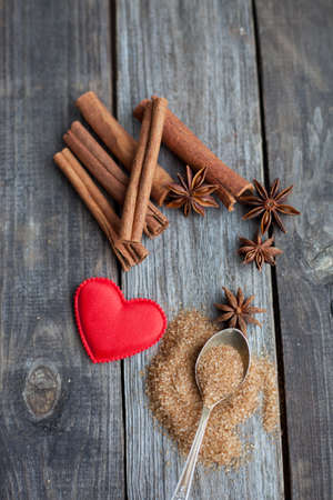 christmas scent: cinnamon sticks and anise stars with spoon of cane sugar on rustic wooden background