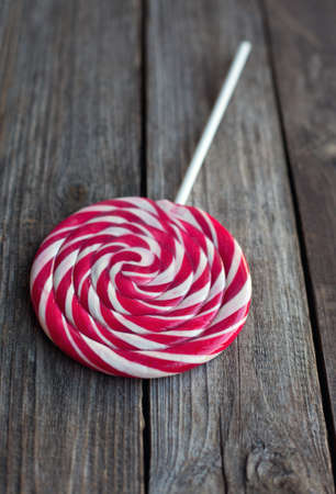 lolli: red and white sweet lollipop on wooden rustic table