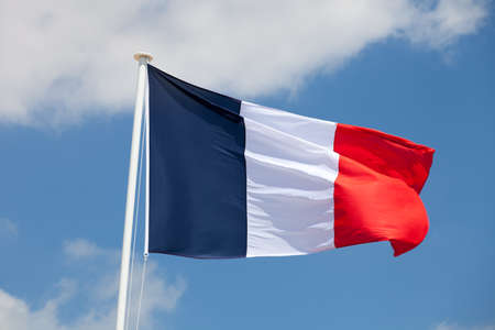 france: French flag against blue sky with clouds