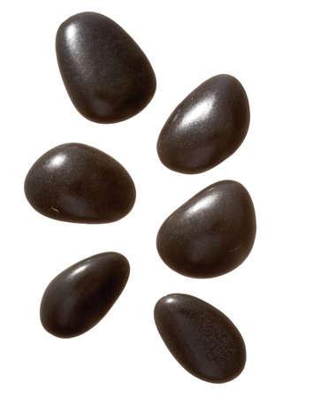 high resolution black massage stones on white background photo