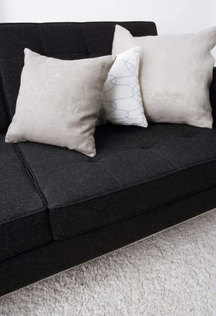 indoor setting, gray pillows laying on a black sofa photo
