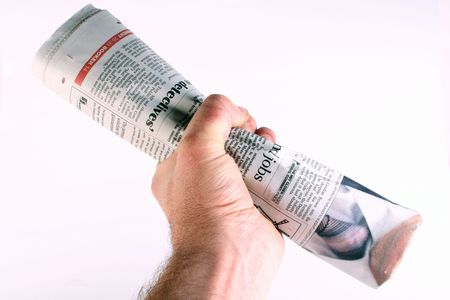 closed fist: Rolled up newspaper in a closed fist.