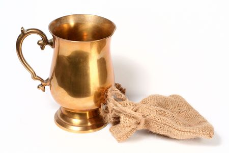 hessian bag: A brass cup and hessian bag on whitw background.