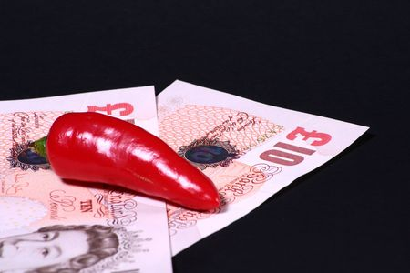 sumptious: Ten pound notes and a chilli. Stock Photo