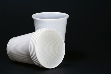 plastic cup: Two White plastic cups isolated on black surface. Stock Photo
