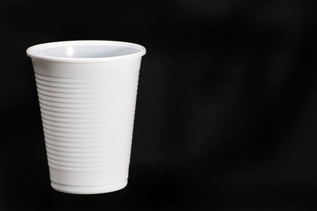 White plastic cup isolated on black surface.