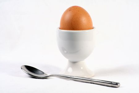eggcup: A egg, eggcup and spoon isolated on white background.